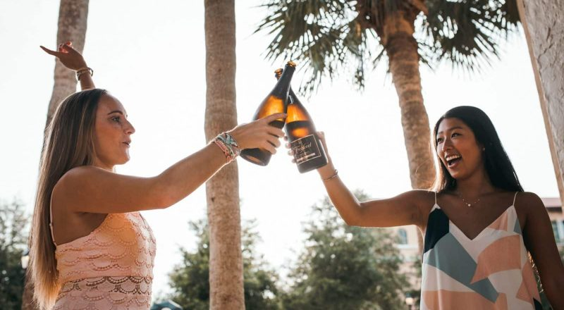 two woman holding beer bottles