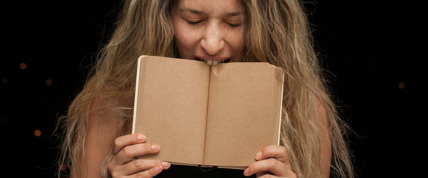 woman covering her face with brown book