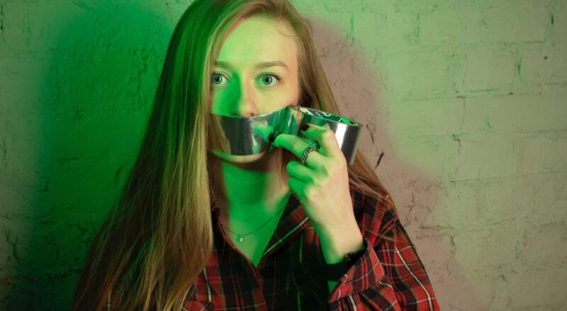woman placing duct tape on her mouth