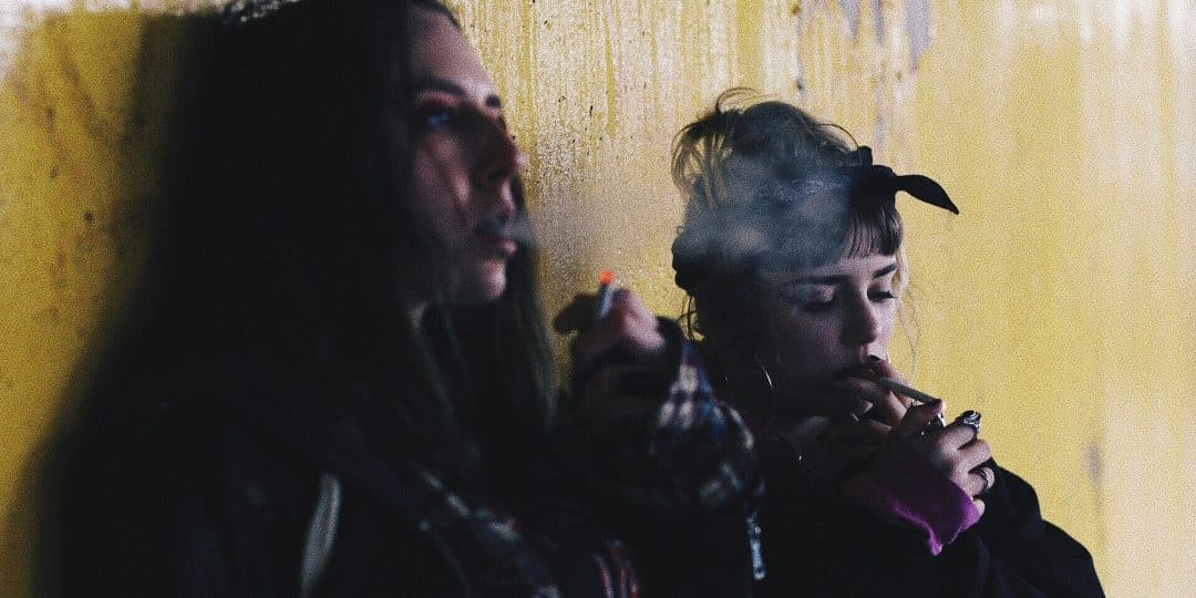 two women smoking while leaning on yellow wall