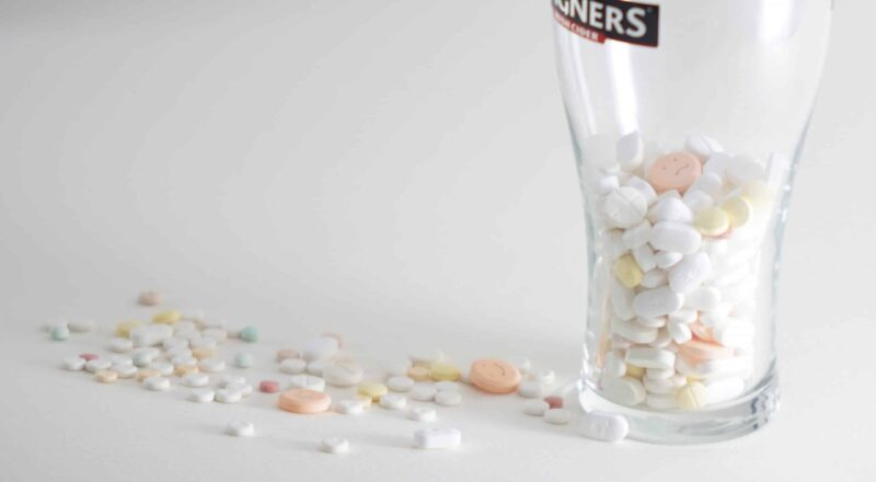 assorted medication pills in clear highball glass