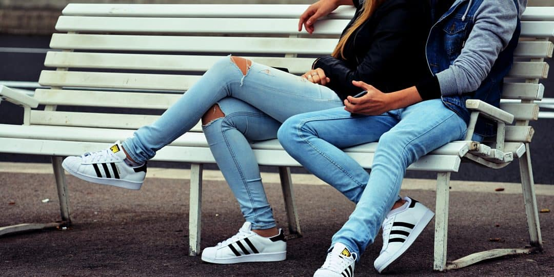 photo of couple sitting on white bench