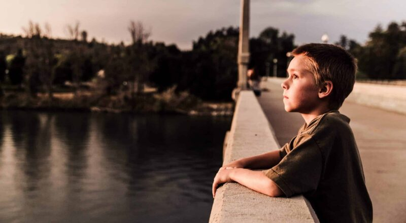 selective focus photo of boy at the bridge near body of water