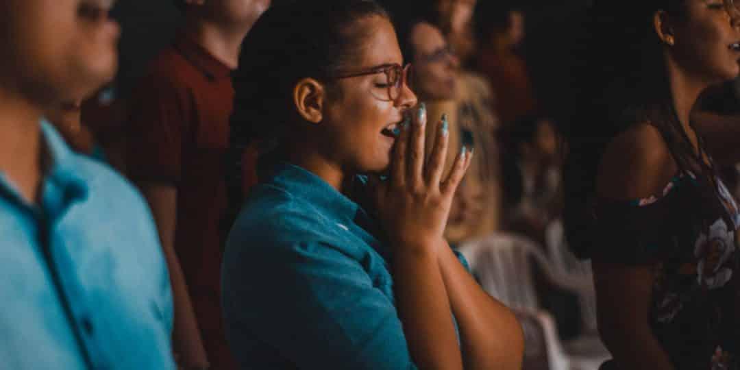 woman praying while closing her eyes