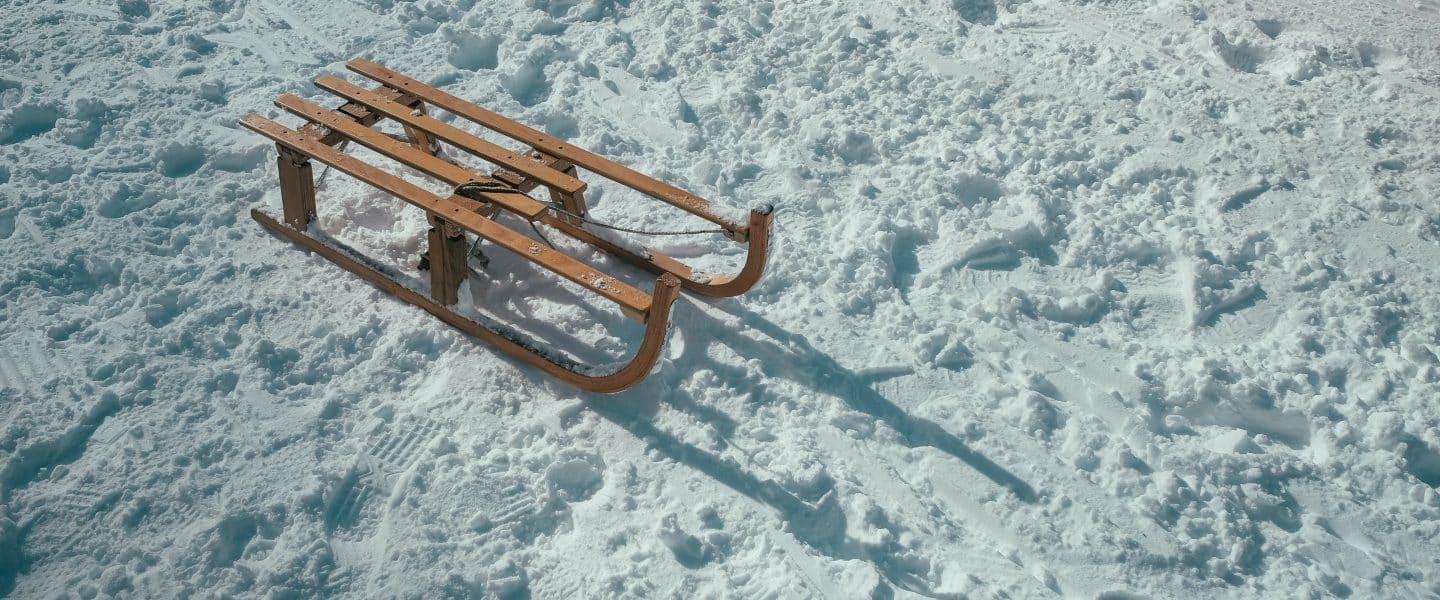 brown sled on snow during daytime