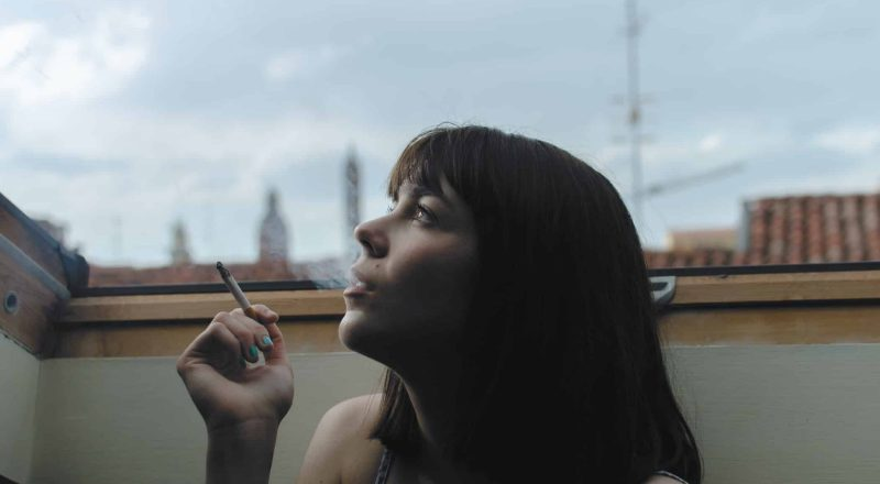 woman holding stick cigarette during day time